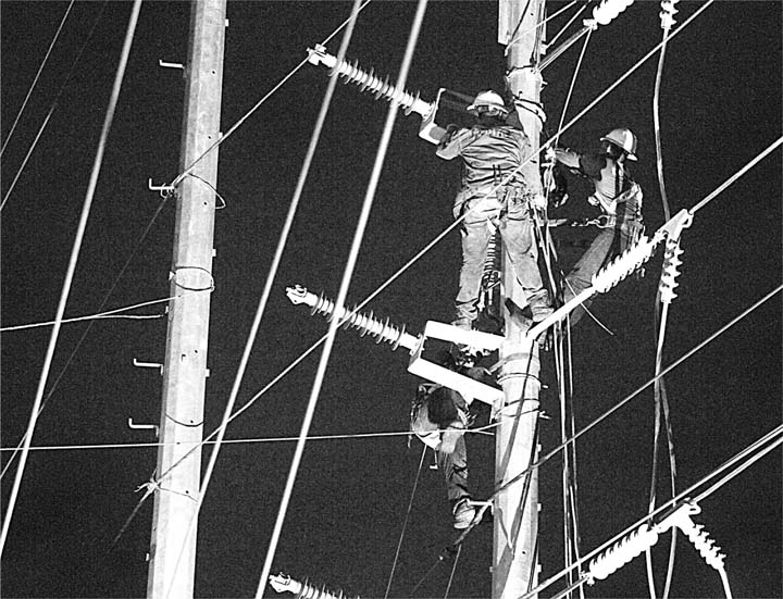 Linesmen of the Davao Light and Power Company stand perilously on cables about 40 feet from the ground as they install power lines on this newly-erected post in Lanang, Davao City in the wee hours of Saturday. The next posts were put up to accommodate the road widening in the area. (Keith Bacongco/ Manila Bulletin)