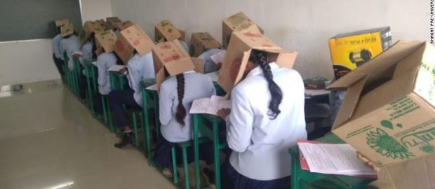 Indian students wear boxes on their heads during exam
